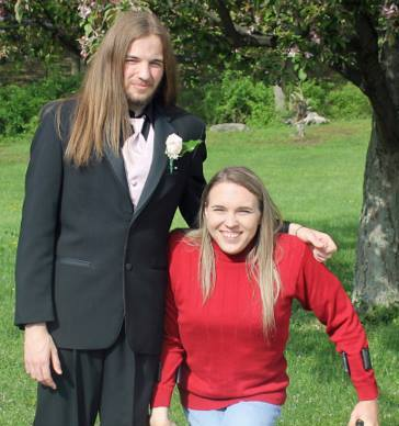 Mom and son posing for a photo outside before son goes to prom