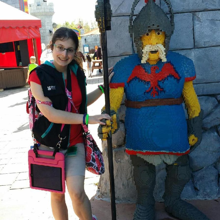 Woman standing next to a statue of a guard made of Legos