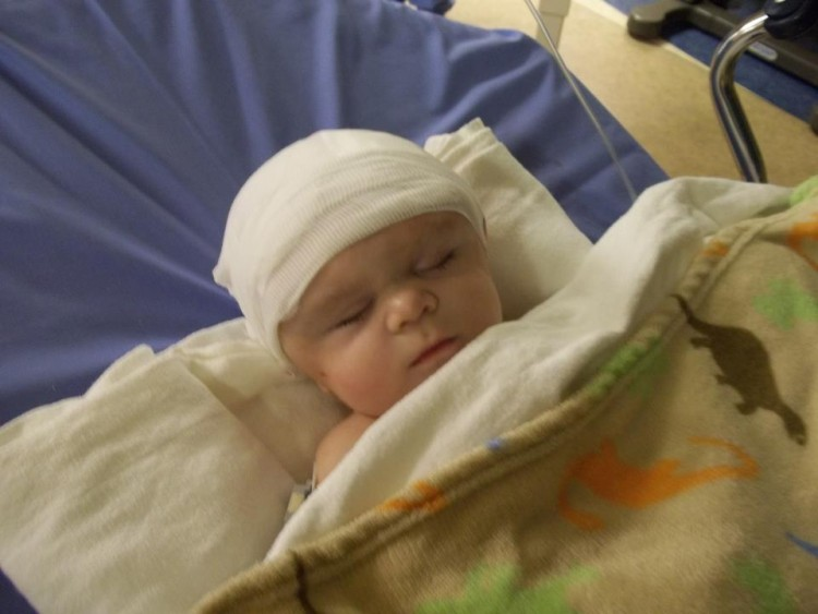 baby with bandage on head in hospital