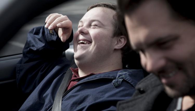 man laughing in passenger seat of car