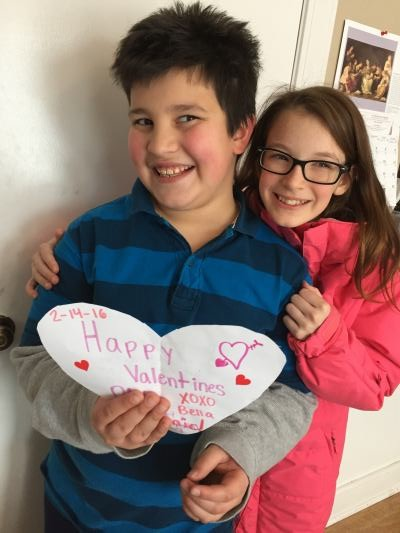 girl posing behind boy holding a heart-shaped Valentine's card