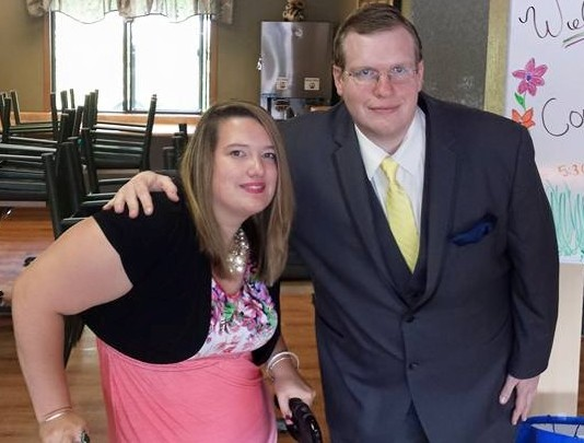 Couple posing for photo at friend's wedding