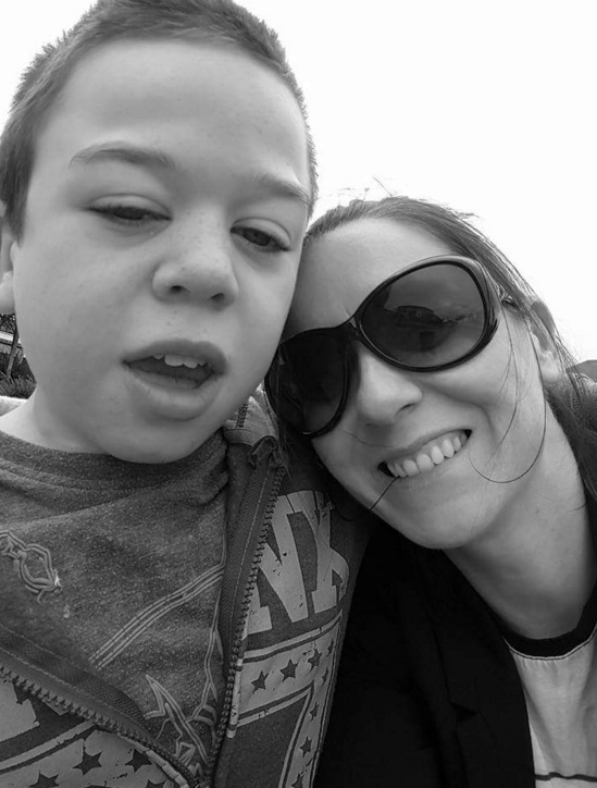 black and white photo of mom in sunglasses and her son. She has her head on her son's shoulder.