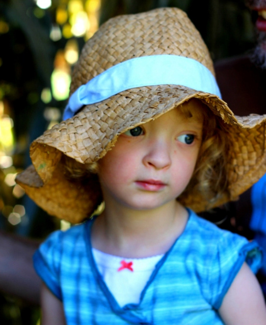 Girl in a wide-brimmed straw hat, looking off to her left.
