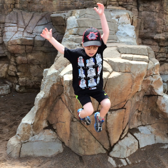 boy wearing baseball cap jumping near a rock