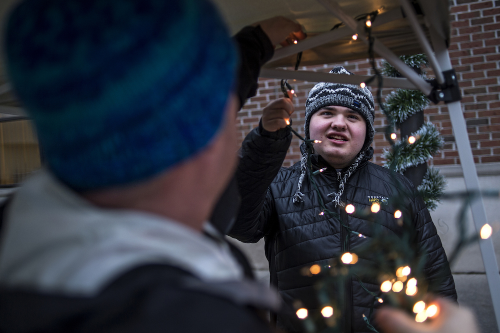 Dennis Mashue, left, strings lights though their booth at Midland's Winter Village as son Tucker Mashue, 17, right, helps on Dec. 17. Together Dennis Mashue and his son Tucker Mashue, 17, run Tuck's Tooques, a pro-autism microbusiness, which helps Dennis teach Tucker entrepreneurship skills by selling handmade Nepalese winter hats.