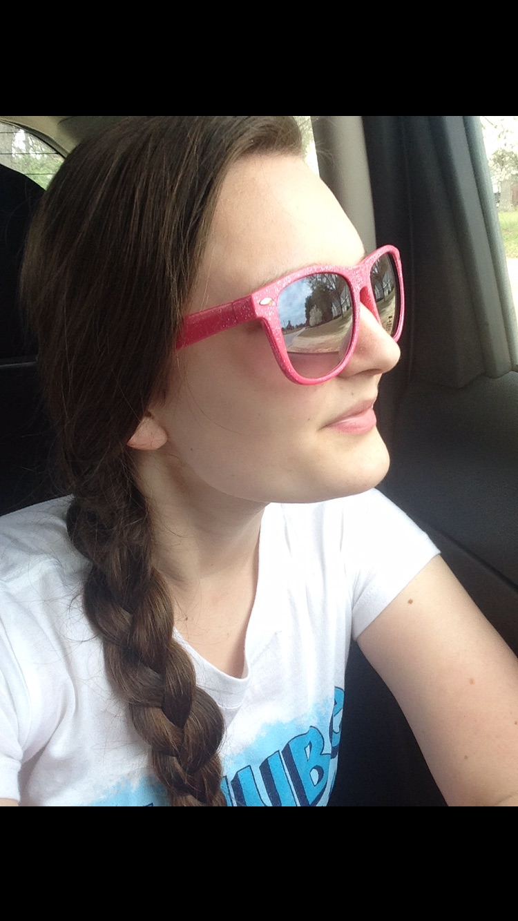 woman with a single braid wearing a white t-shirt and sunglasses