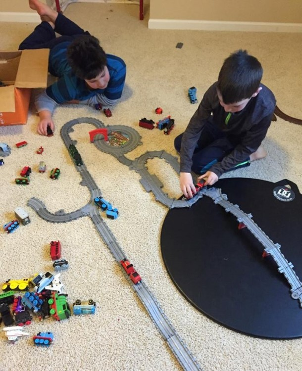 boys playing with a toy train set on the floor