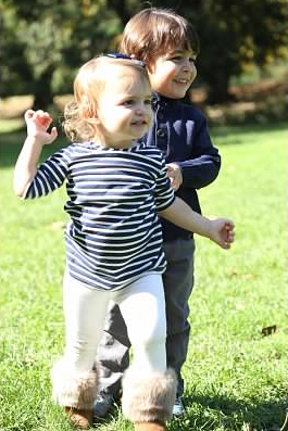 toddler boy and girl running on grass