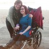 Two women on the beach. One woman is in a wheelchair, and the other woman is standing next to her and has her arm wrapped around her. Their heads are touching and they are smiling.