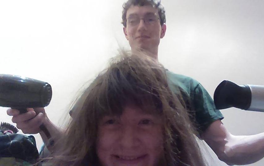 man blow-drying woman's hair