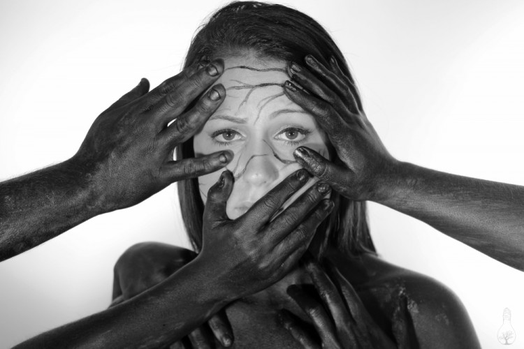 The black hands now cover the woman's face.
