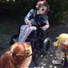 friends playing with puppets for girl in wheelchair