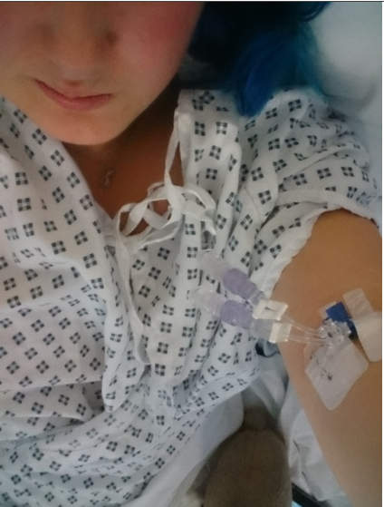 woman in hospital gown showing needle in arm