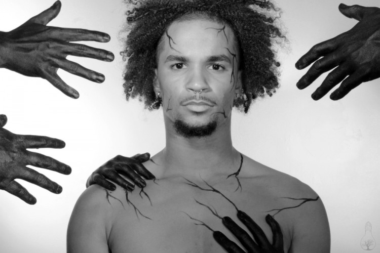 Man staring at the camera. Black hands are reaching out at him.