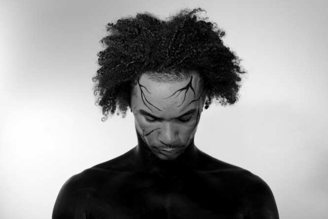 Man with black make up on his body, looking down.