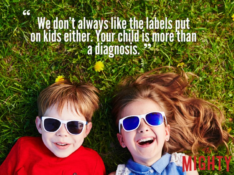 Boy in girl laying in grass wearing sunglasses and reads 'we don't always like the labels put on kids either. Your child is more than a diagnosis.'