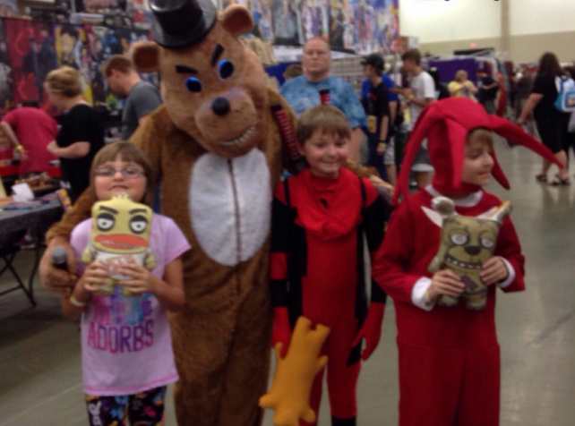 Kids posing with person in a bear costume at a comic convention