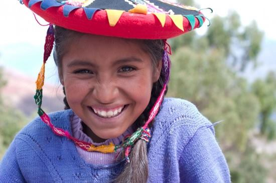 Girl in a colorful hat, smiling.
