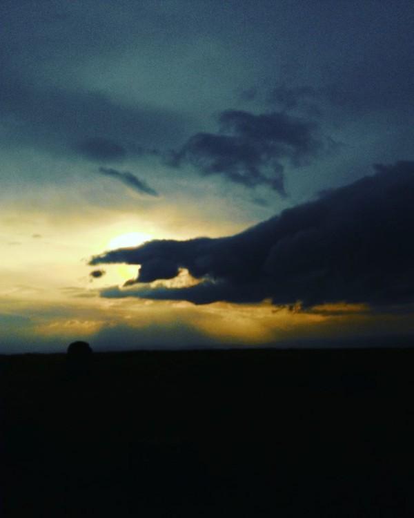 A dark sky. The sun is behind a cloud.