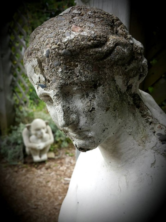 A stone woman. Pieces of her head are crumbling.