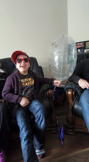 boy on couch holding balloon