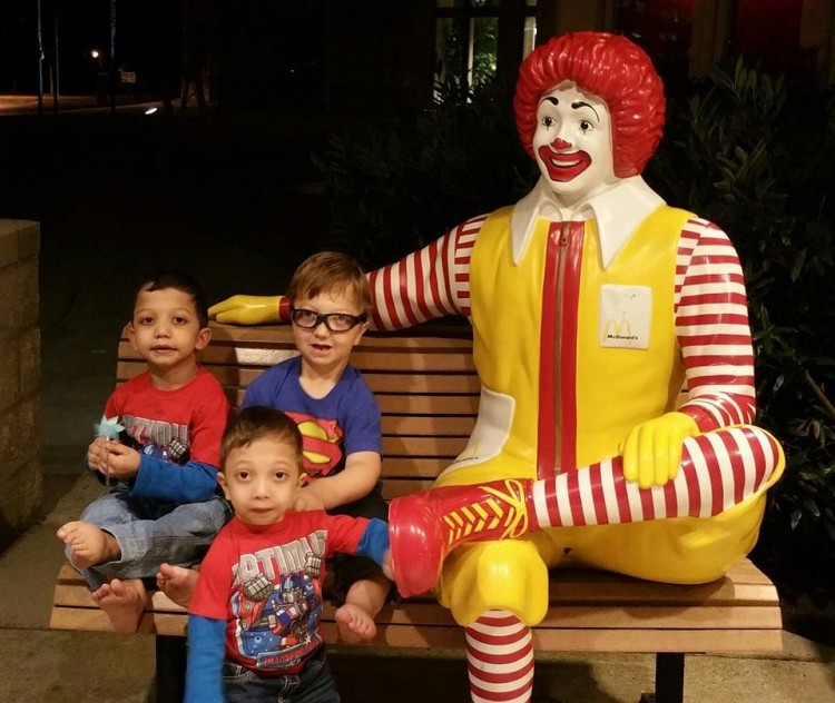 three young boys on bench next to ronald mcdonald