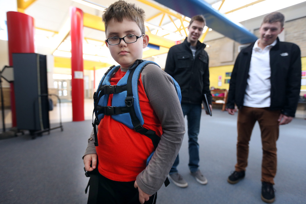 Liam Craig tried on a backpack designed for children on the autism spectrum by University of Minnesota students Will Radke left and Jake Portra March 3, 2016 in Woodbury, MN. ] Jerry Holt/Jerry.Holt@Startribune.com
