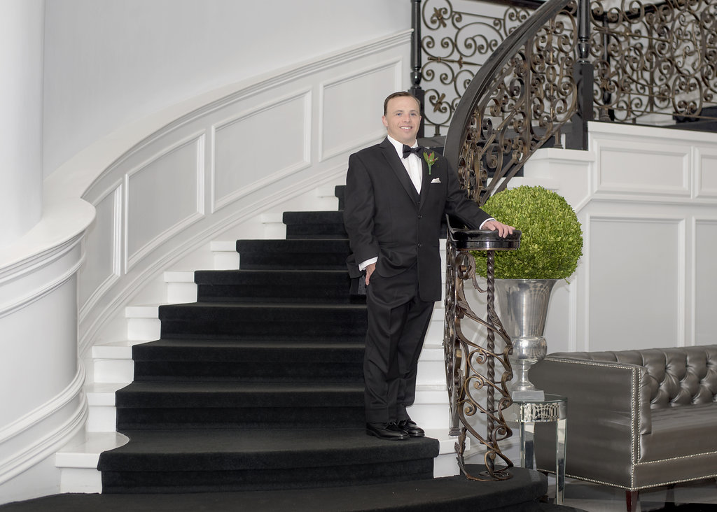 another young man in tux on stairs