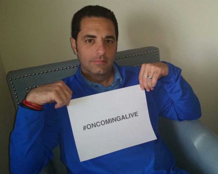 """Dari Nowkhah holding """"On Coming Alive"""" sign"""
