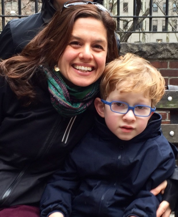 boy wearing blue glasses next to woman with dark hair