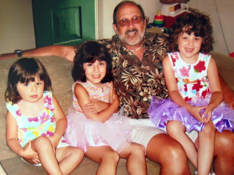 grandfather sitting on couch with three young girl grandchildren