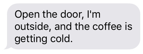 Text message that says [Open the door, I'm outside, and the coffee is getting cold.]