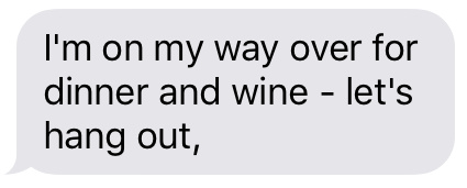 Text message that says [I'm on my way over with dinner and wine — let's hang out.]