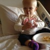 Little girl in hospital bed drinking a beverage