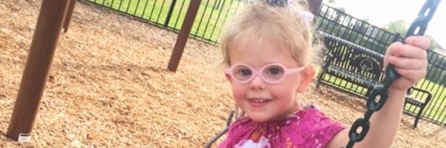 little girl in glasses on a swing