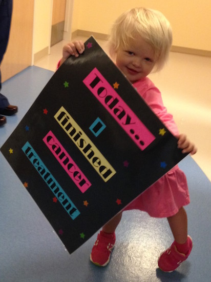 "Little girl holding sign that says ""Today... I finished cancer treatment"""
