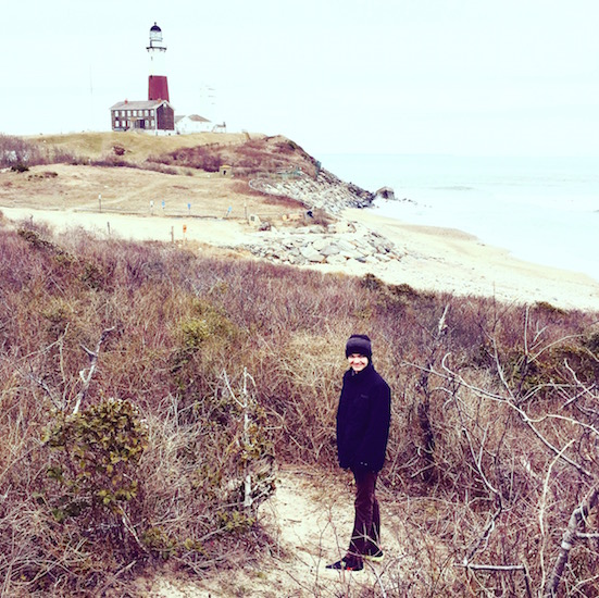 boy standing in front of lighthouse