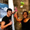 two men smiling in front of rock climbing wall