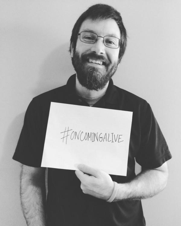"Joe Kowalisyn holding ""on coming alive"" sign"