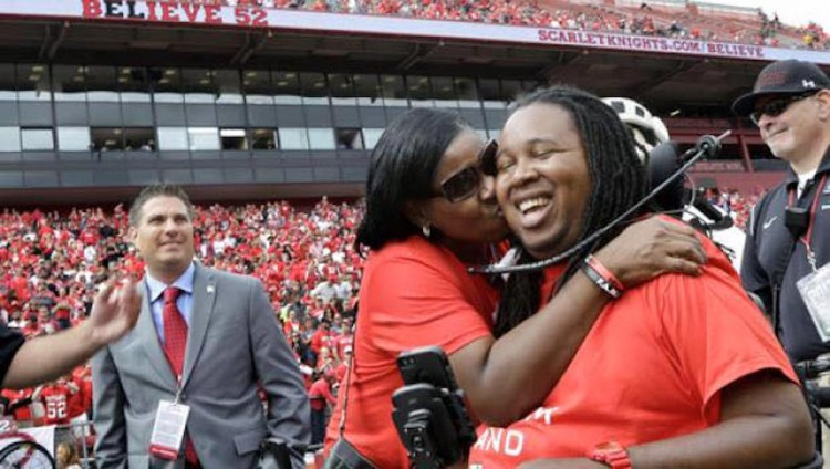 mother kissing her son on the cheek in stadium full of people