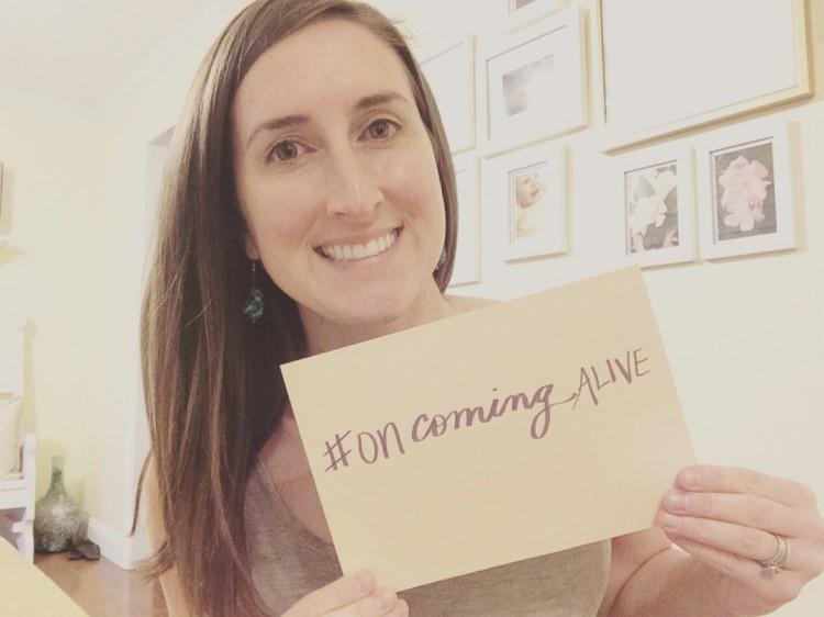 "Lauren Johnson holding ""on coming alive"" sign"