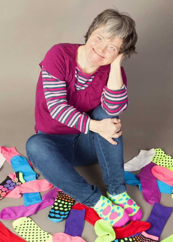 woman sitting and smiling in pile of socks