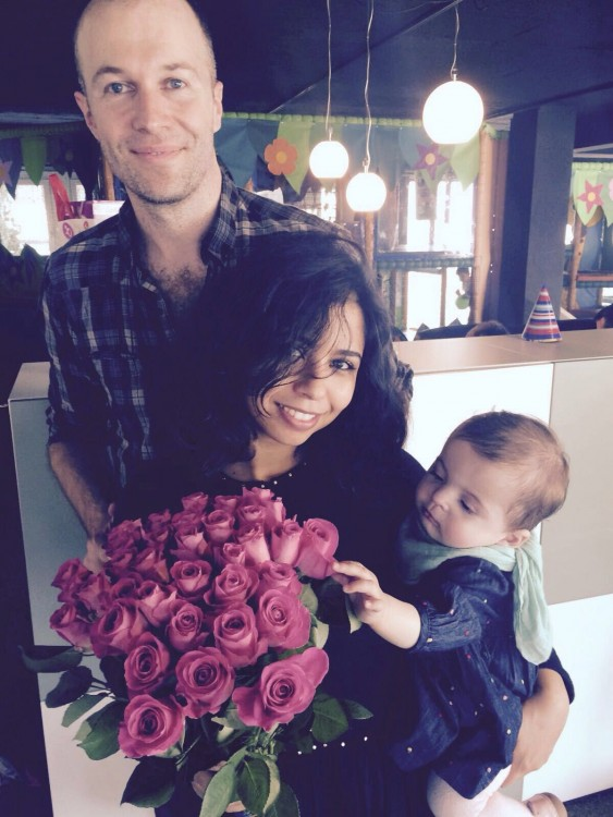 Sanaa, her husband, and daughter Mia pose with a bouquet of flowers.