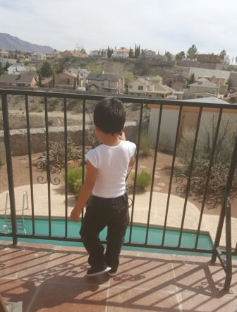 son standing on balcony looking at pool