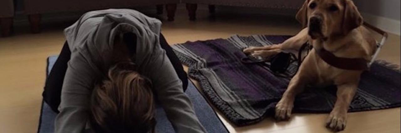 woman doing yoga beside guide dog