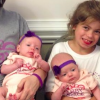 little girl sitting with triplet babies