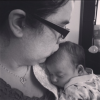 A black and white photo of Noel kissing her new born baby.
