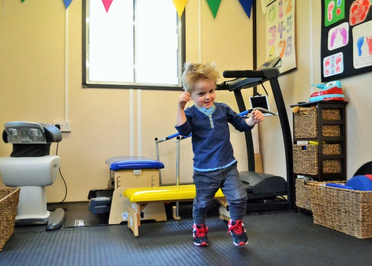 young boy learning to walk in his gym