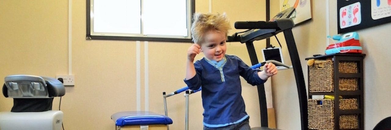 young boy learning to walk in the gym